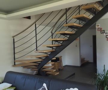 Escalier limon central 1/4 tournant en acier thermolaqué. Rampe acier, main-courante inox brossé, marches en bois huilées cirées